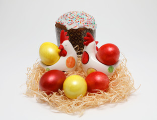 Colorful Easter eggs and two toy hens in a nest and Easter cake on white background, Spring Image. Easter concept.