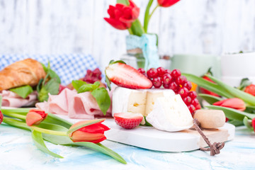 Sweet spring breakfast with croissants and bacon on a light background. A bouquet of red tulips and fresh berries of strawberries and currants. The concept of holiday celebration. brie