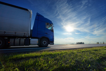 Fotobehang - Blue truck driving on the asphalt road on a horizon against the glowing sun