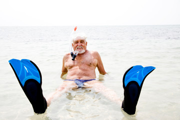 Senior man on beach vacation snorkel and flippers relaxing in sea smiling at camera
