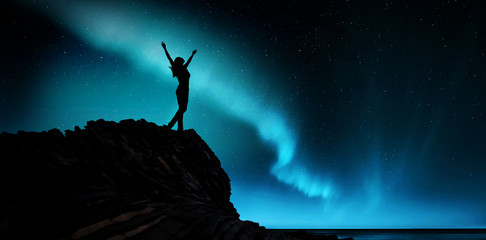free and happy woman raises her arms at the aurora borealis
