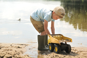 Five years old boy playing with a small truck on a summer lake beach.