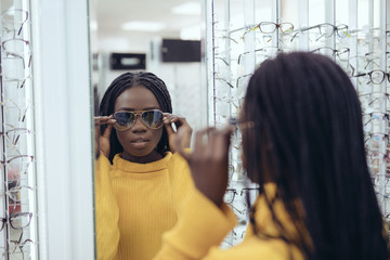 Young pretty african woman in yellow sweater choose sunglasses in Ootician's shop