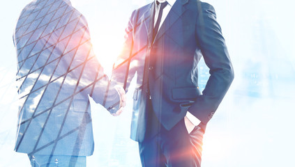 Two businessmen shaking hands in blue city Wall mural