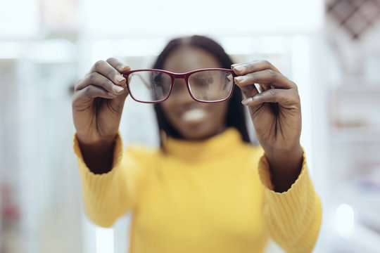 Young african woman pointed eyeglasses frames in Optical Store. Cute girl deciding for glasses of different shapes and colors for buy