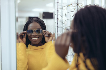 Young pretty african woman try sunglasses in optical store
