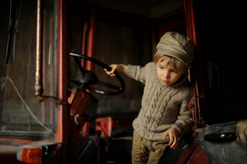 Little boy farmer in a tractor. The child is interesting how the machine works.