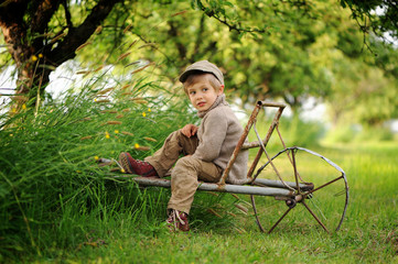 A little boy in an apple orchard. Holiday in the countryside. A memory of a carefree childhood.