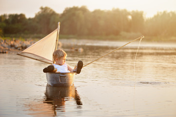 The boy is fishing in the middle of the lake, lying in a tub with a mast, legs outstretched in galoshes. Warm rays of the setting sun, sunny summer, holidays, carefree childhood.
