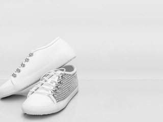 Women's white studded stylish shoes with a plain background for copy space.