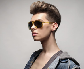 The beautiful young man in sunglasses on a white background. Fashion concept.