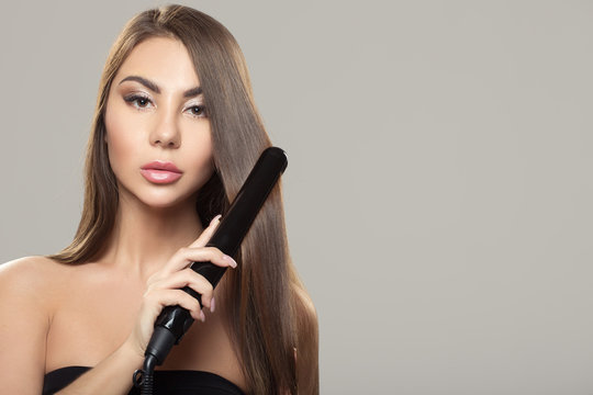 Hairdressing. Iron hair straightening. Beautiful woman with long straight hair. Healthy hair. Hairstyle