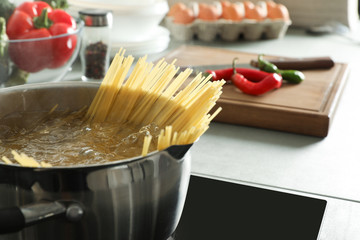 Cooking spaghetti in pot on electric stove, closeup. Space for text
