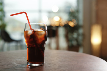 Glass of cold cola on table against blurred background. Space for text
