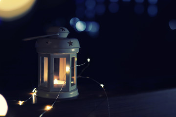 Lantern and Christmas lights on wooden railing outdoors against blurred background, space for text. Winter night