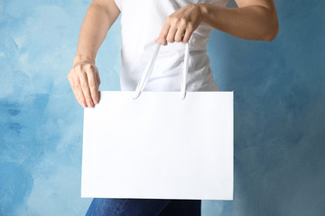 Woman holding mock-up of paper shopping bag on color background