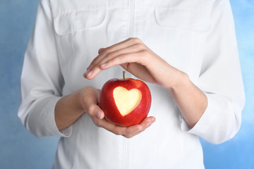 Woman holding apple with carved heart on color background, closeup