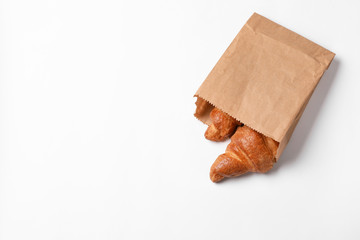 Paper bag with delicious croissants on white background. Space for text