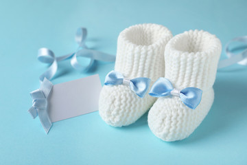Handmade baby booties and empty greeting card on color background