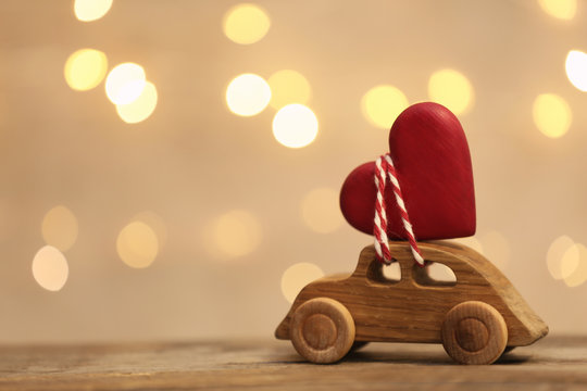 Toy car with red heart on table against blurred lights. Space for text