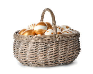 Wicker basket with traditional Easter eggs on white background