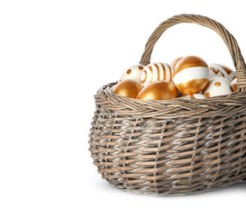 Wicker basket with traditional Easter eggs on white background, space for text