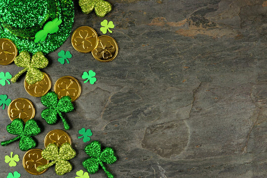 St Patricks Day side border with shamrocks, gold coins and leprechaun hat over a dark slate background