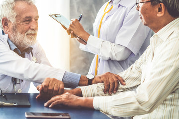Senior male doctor talking to elder man patient in the hospital office. Medical healthcare and doctor staff service concept.