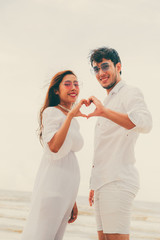Young couple shows heart shape hand gesture on the beach in summer.
