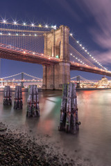 View on Brooklyn bridge at night from East River with long exposure