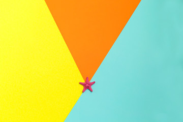 One pink starfish on colorful background. Top view. Summer time. Sea style. Creative concept.