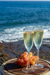 Champagne, prosecco or cava served with pink grape in two glasses on outside terrace with sea view