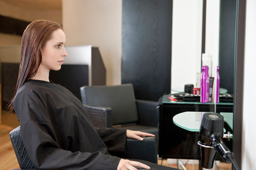 Female client in chair looking in mirror at hairdressing salon