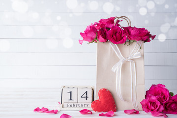 Valentines day and love concept. Pink roses in paper bag with February 14 text on wooden block calendar on white wooden background.