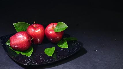 Ripe apple with leaf on black plate. Fruit image