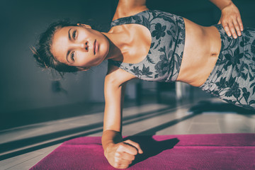 Home fitness side plank exercise Asian woman in fashion activewear planking bodyweight exercises on yoga mat. Woman doing core body exercising for toned abs stomach.