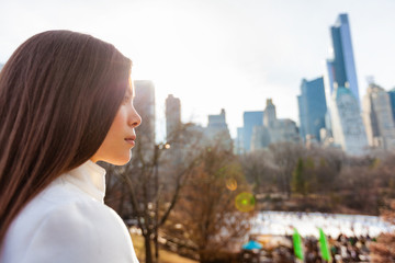 New York City Asian woman walking in winter in Central Park by the skating rink pensive looking at NYC skyline background. Urban city lifestyle living people outdoor.