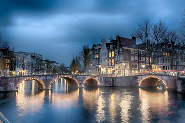 Keizersgracht inersection bridge view of Amsterdam canal and historical houses during twilight time, Netherland.