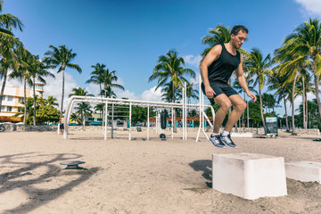 Squat jump on training box in outdoor beach gym. Man athlete training workout at Fitness bench jumping outside summer american South Beach Miami city. Strength training fit male working out outdoors.