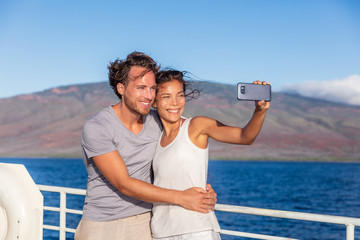 Wall Mural - Cruise ship couple taking selfie phone photo Travel in Hawaii holiday. Two tourists lovers on honeymoon travel enjoying summer vacation.