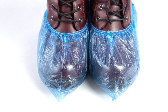 Boots in blue shoe covers on white background. Hygiene and cleanliness in medical institutions