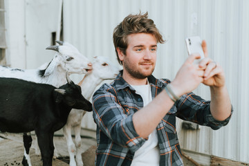 Happy man taking a selfie with baby goats