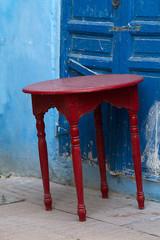 Roter Tisch vor blauer Hauswand in Marokko.