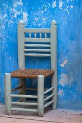 Kleiner Stuhl vor blauer Wand in Marokko.