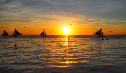 Silhouette scenery of sunset in the sea and traveler on sailboat Boracay Island, Philippines