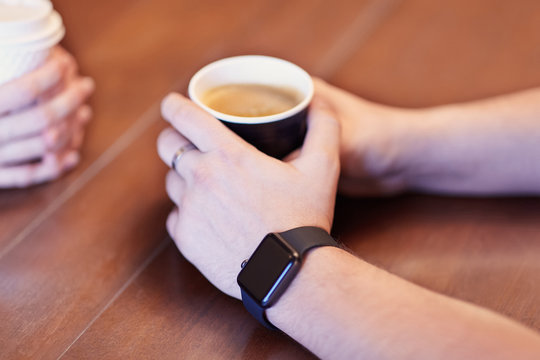 The man hands with black electronic watch, holding black cup of coffee. Other hands on background with white cup, wooden table. Date or friends meeting, cosy atmosphere. Selective focus, copy space.