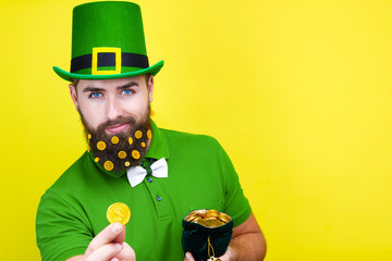 Happy young adult man male in green shirt, green leprechaun hat and tie bow with gold coins in beard and bag of gold as symbol of Ireland traditional holiday Saint Patrick Day on isolated  background Wall mural