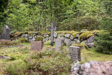 Old semetery in Finland with grave crosses and stones.