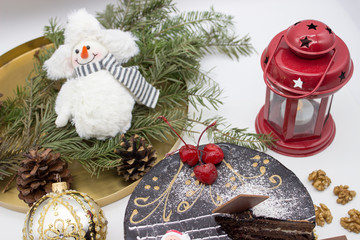 Delicious chocolate cake, decorated cherries, and sugar Santa and crispy nuts, with Christmas decor and ornaments.