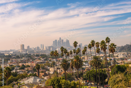 Fotomurales Los Angeles skyline at sunset with palm trees in the foreground